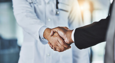 Cropped shot of a doctor shaking hands with a businessman in a hospital